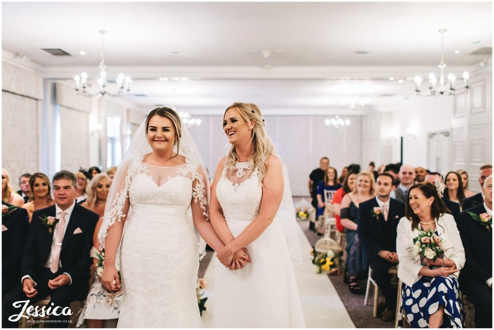 the brides laugh during their wedding ceremony in cheshire