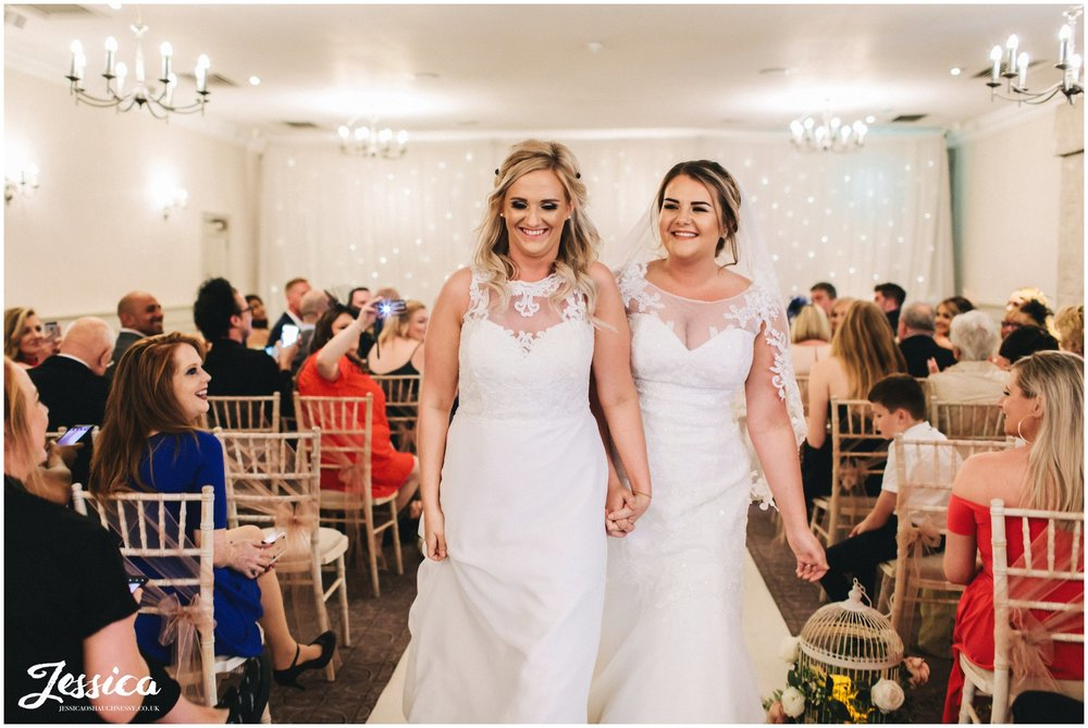 the brides laugh as they walk down the aisle as a married couple