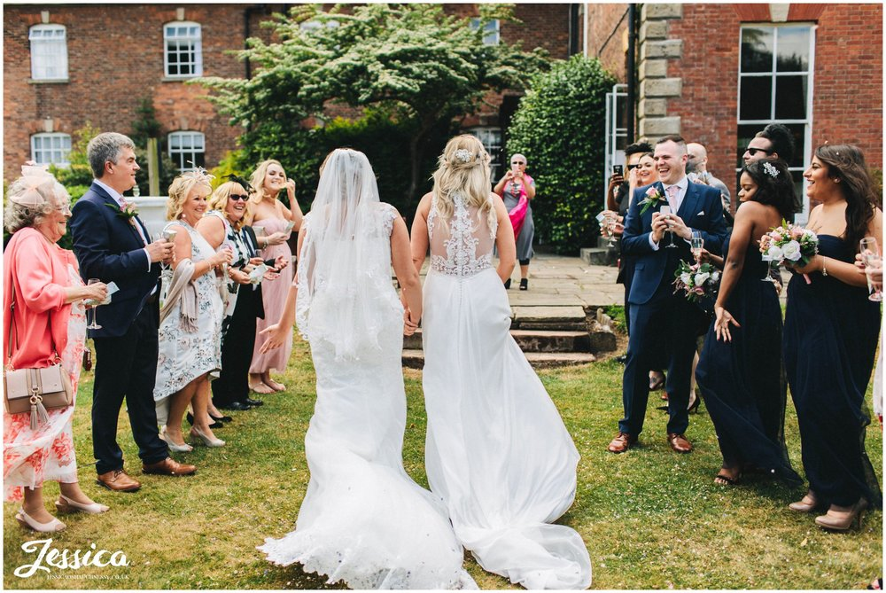the couple walk back through their guests as they cheer