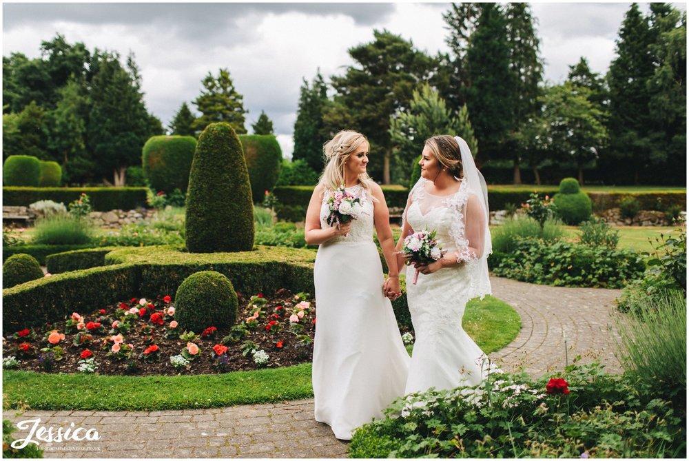 the brides walk hand in hand through mottram hall's gardens