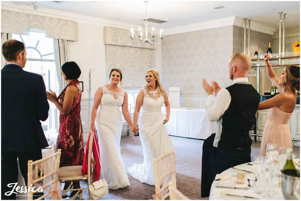 the brides are welcomed in to their wedding breakfast