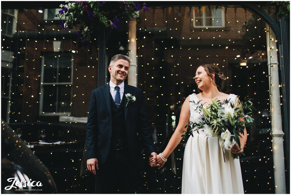 bride & groom hold hands in front of knutsford shop window