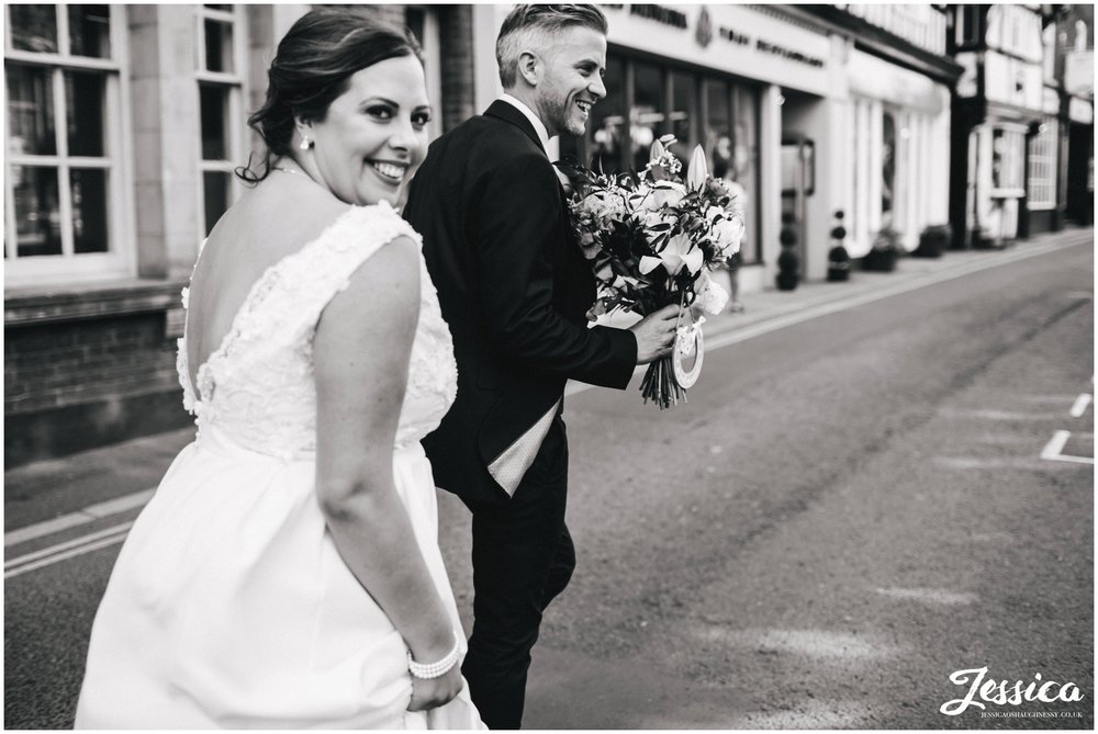 the groom carries the brides bouquet for her whilst walking down the street