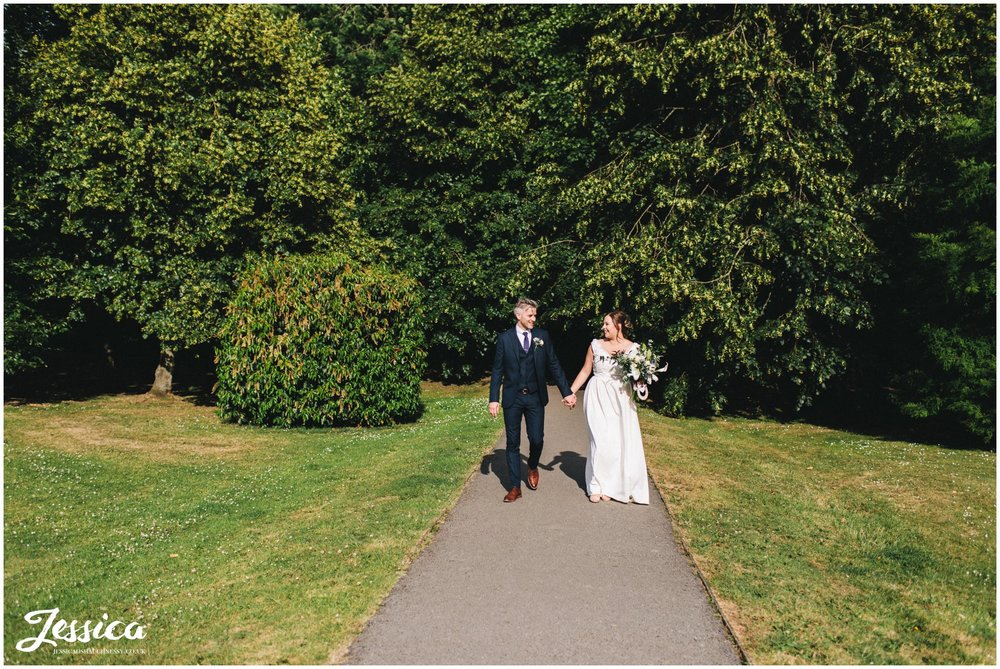 the couple walk hand in hand through the cheshire park in knutsford