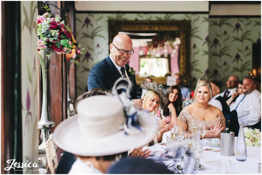 father of the bride laughs whilst giving his speech