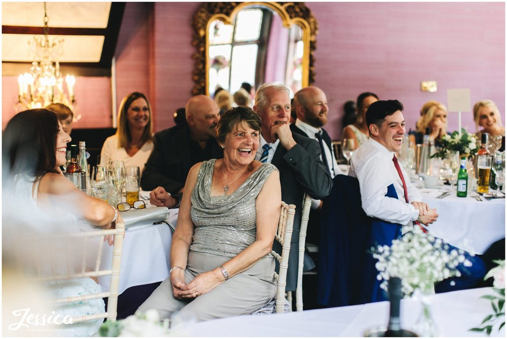 the groom's family laugh along to the speeches in the garden room