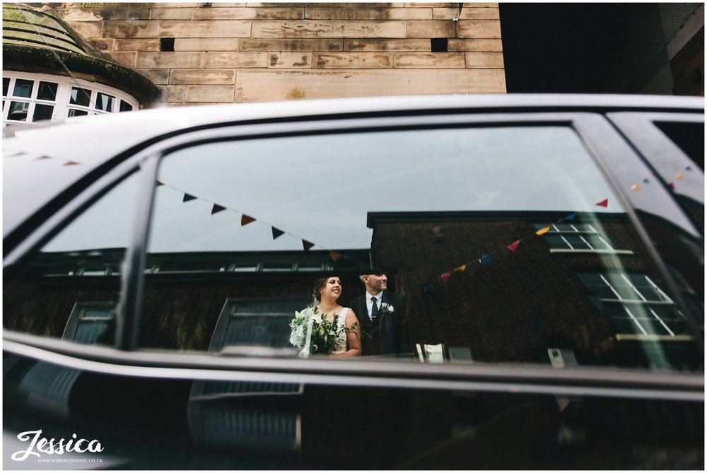 bride & groom photographed through a car window on the busy street