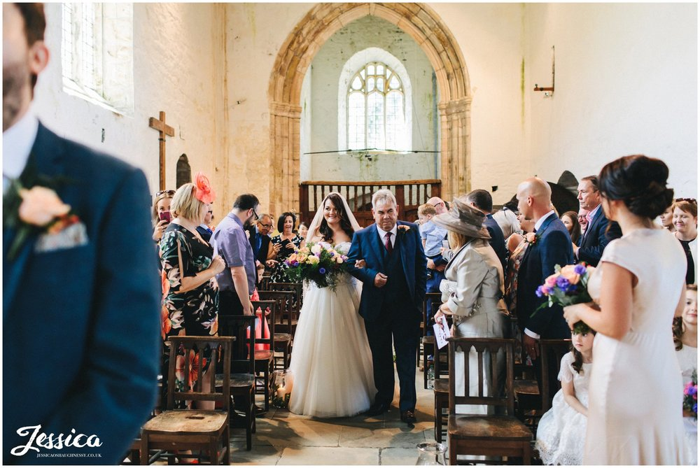 the bride & her father walk down st beuno's aisle