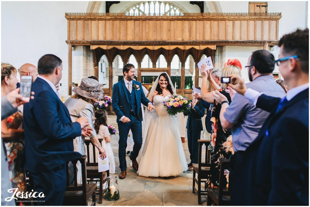 the new husband and wife walk back down st beuno's aisle married