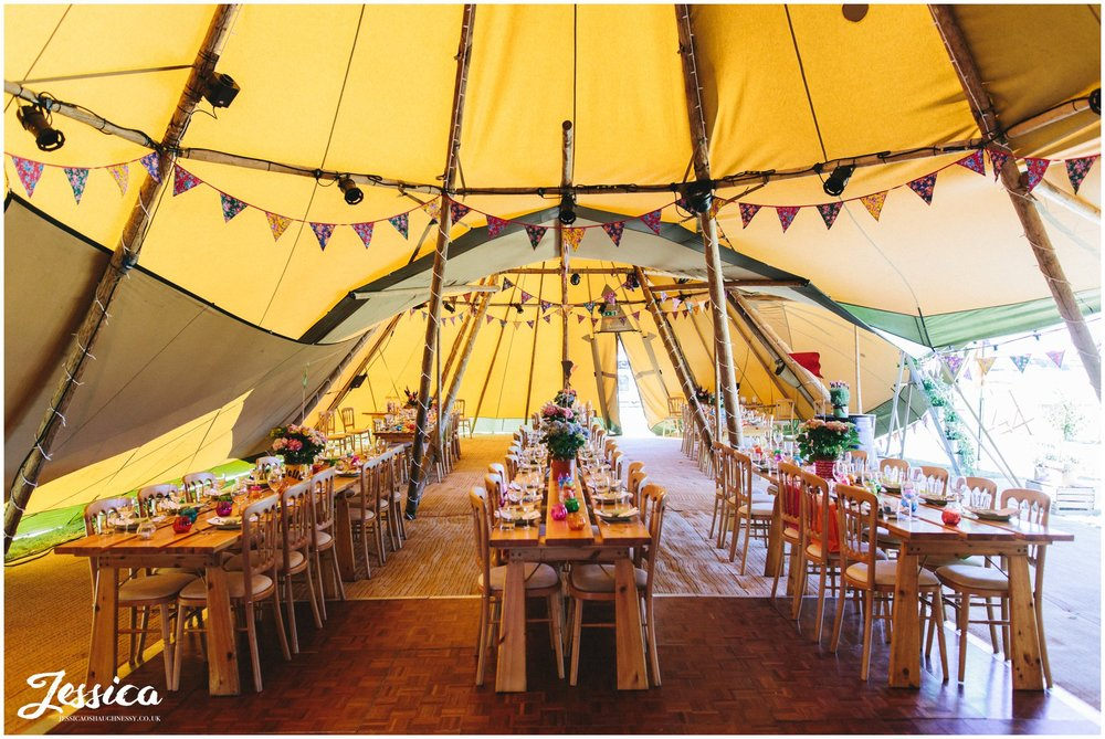 the tipi is decorated in bright colours for the wedding breakfast