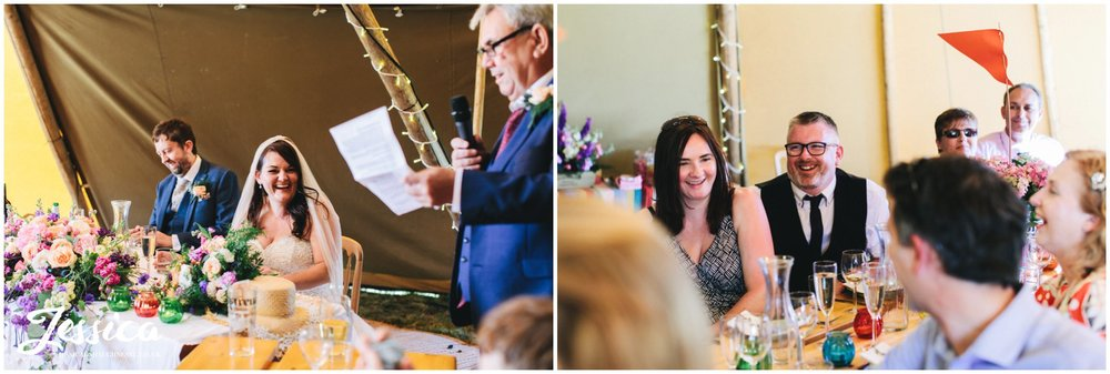 bride laughs whilst her dad delivers his speech