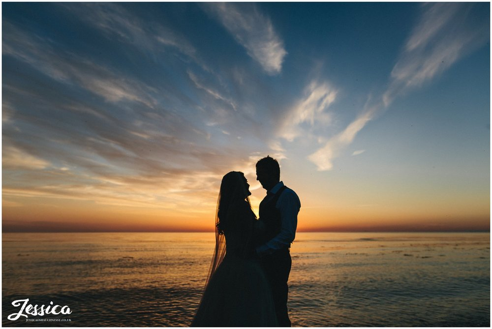 bride & groom stand in front of epic sun set in north wales