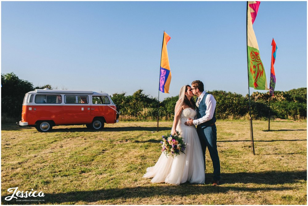 newly wed's kiss in front of vw camper and festival flags