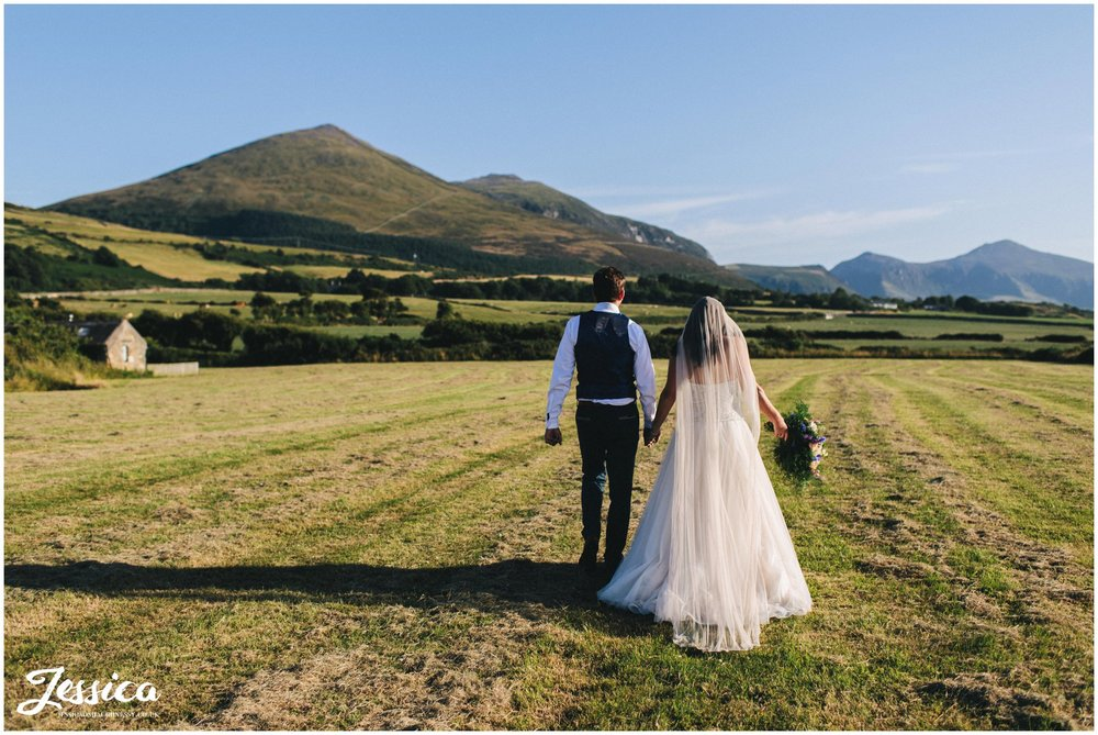 husband and wife walk hand in hand in front of the Welsh hills