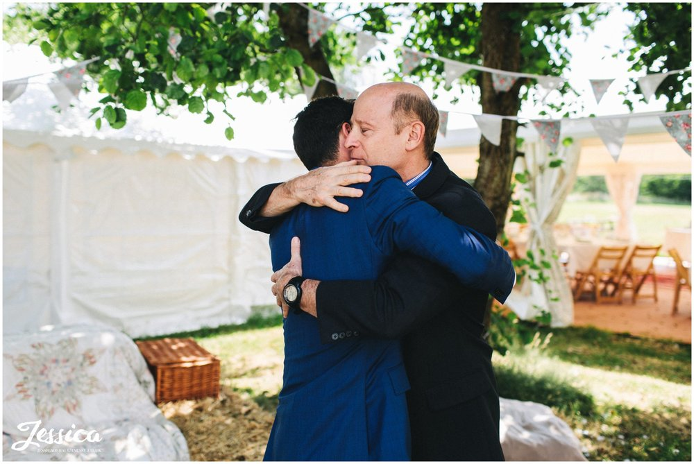 groom hugs his father at hafod farm, a north wales wedding venue