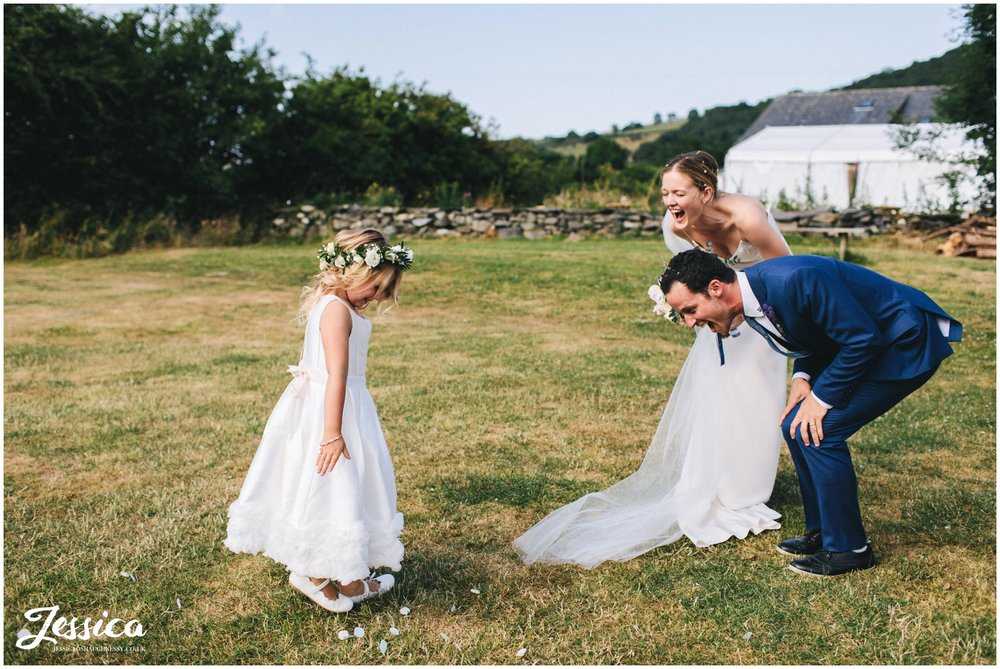flower girl throws confetti over the couple