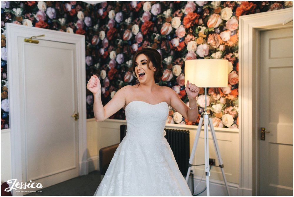 the bride cheers as she puts on her wedding dress