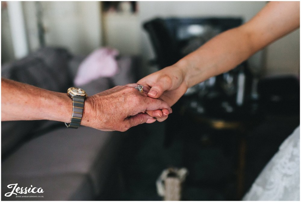 bride holds her mums hand as she gets dressed for the wedding