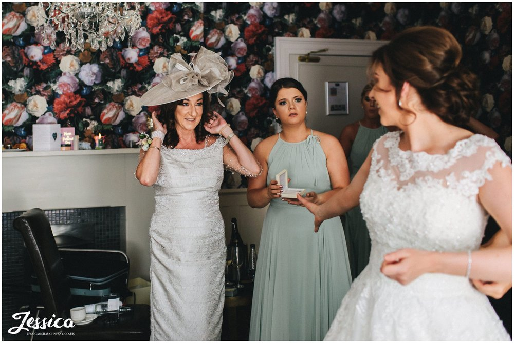 mother of the bride admires her daughter dressed for her wedding