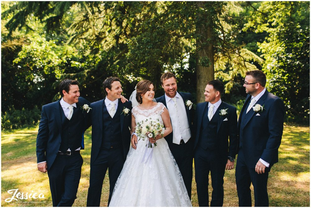 the bride, groom & groomsmen laugh during the formal photographs