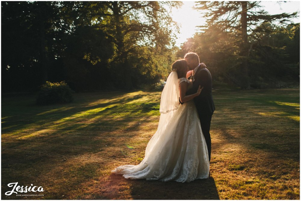 couple kiss in the golden light at the north west venue
