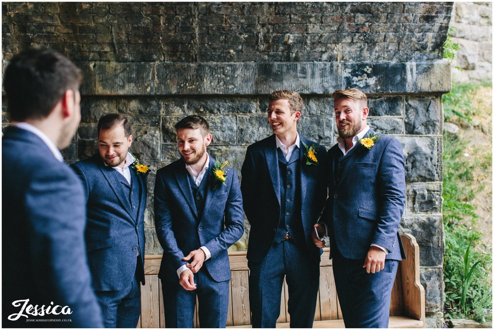 groomsmen laugh as they wait under the bridge