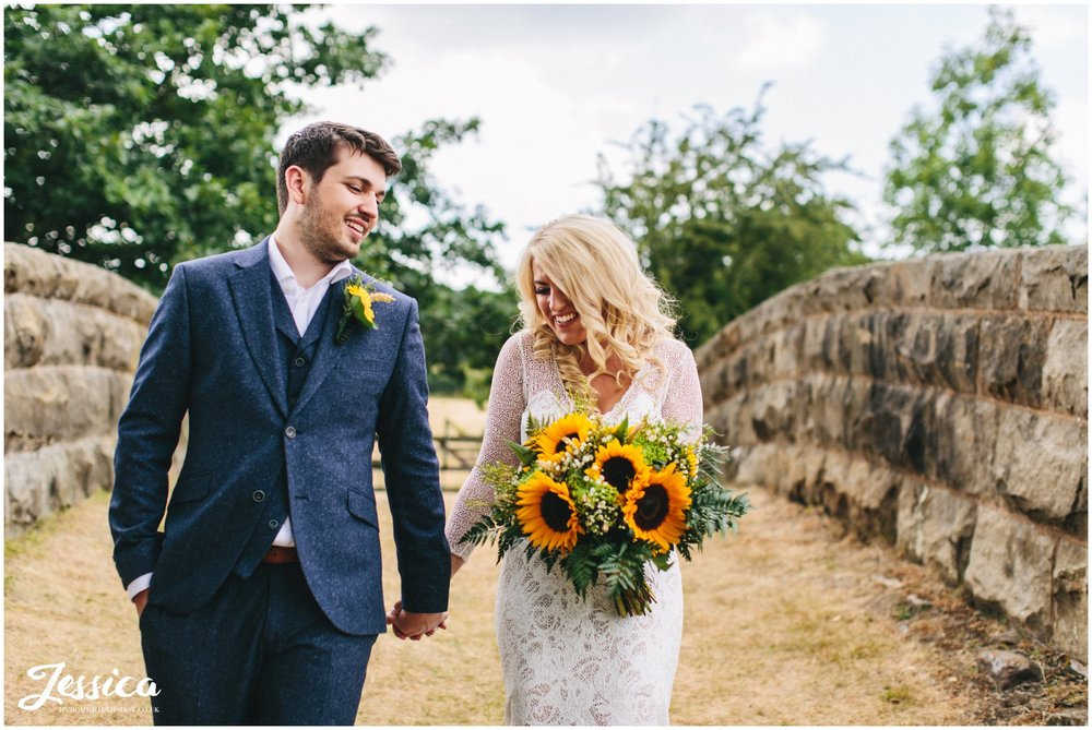 couple hold hands whilst walking through their wedding venues grounds