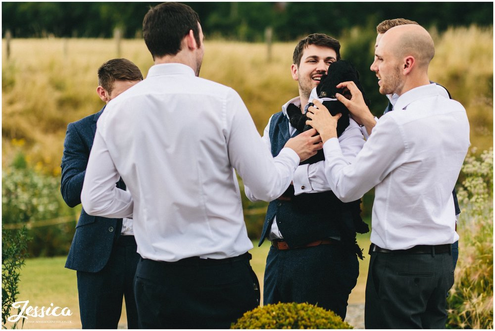 the groom hold one of the puppies