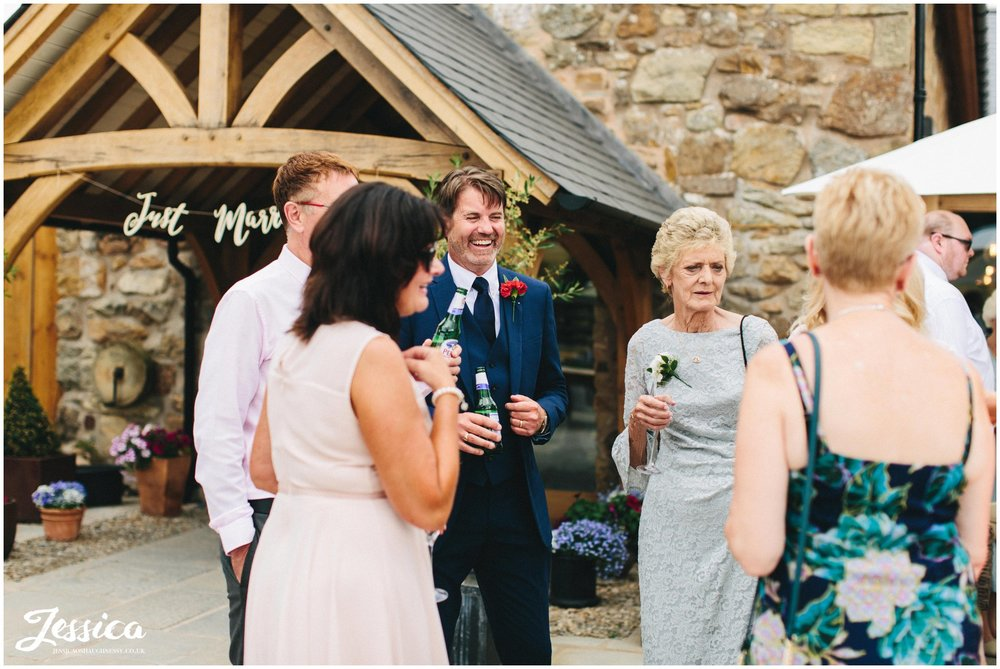 wedding guests laugh together at the drinks reception