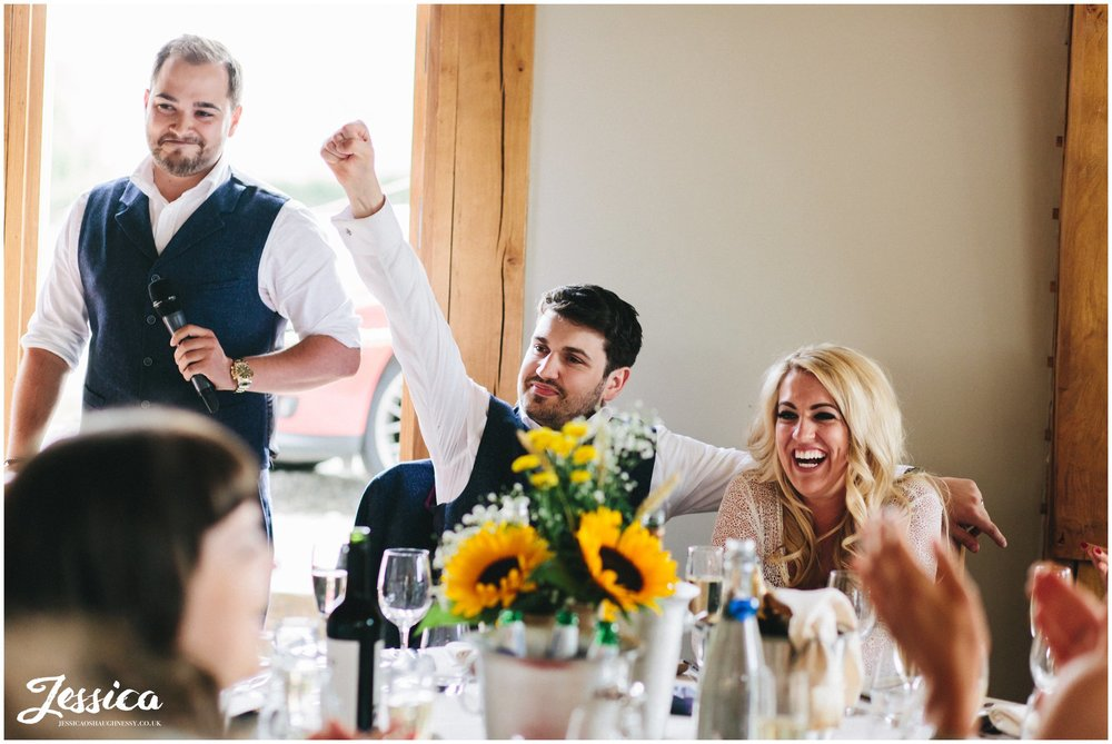 groom cheers during the best man's speech