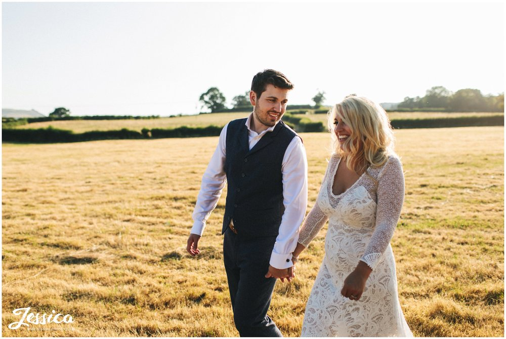 newly wed's walk through fields in golden hour