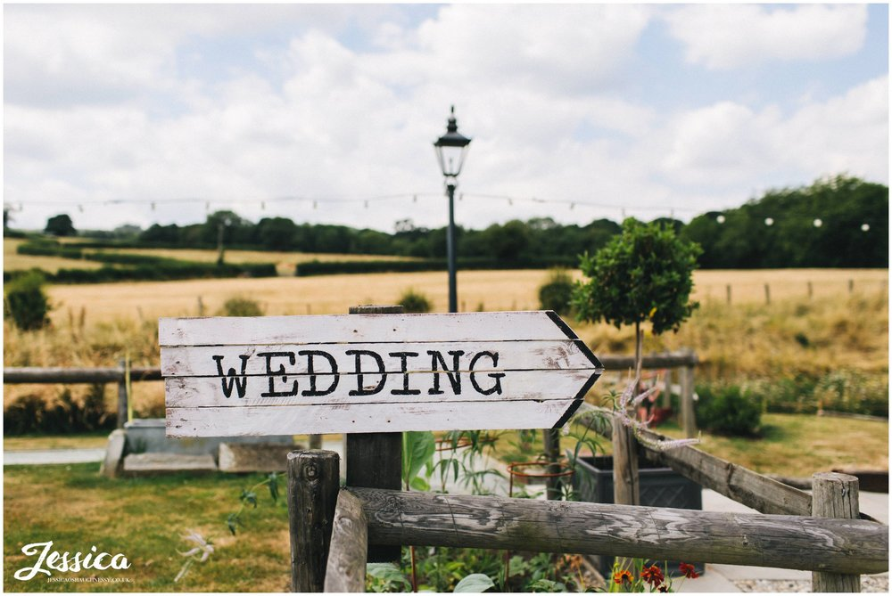 wedding sign pointing guests to the ceremony under the bridge