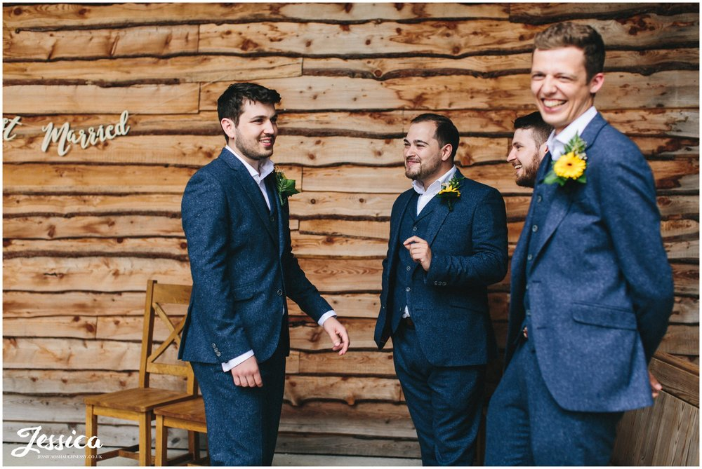 the groom laughs with his groomsmen before the ceremony at tower hill barns