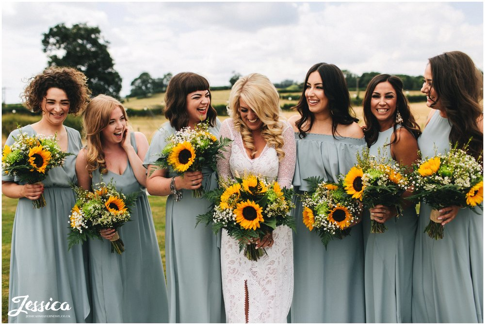 bridesmaids & bride laughing holding sunflower bouquets