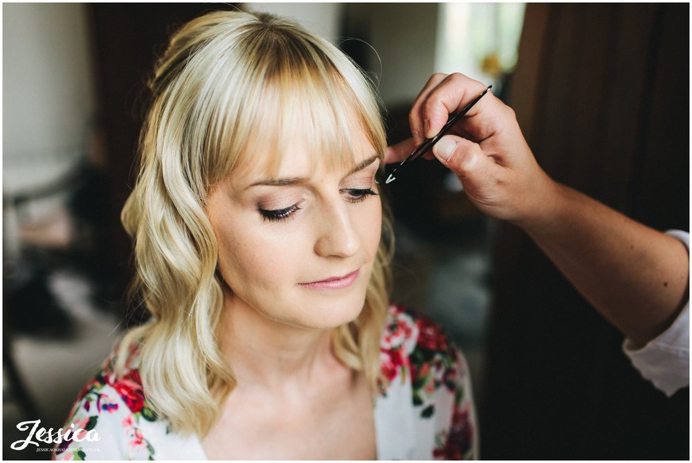 the bride has her makeup done on her wedding morning