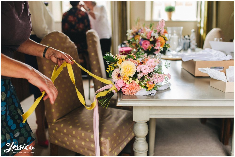 ribbons are tied to the brides bouquet