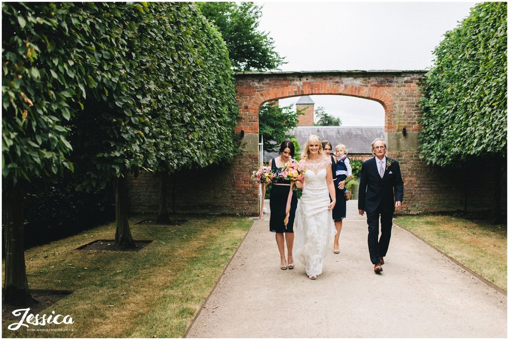 bride & her father walk down the tree lined path at combermere abbey