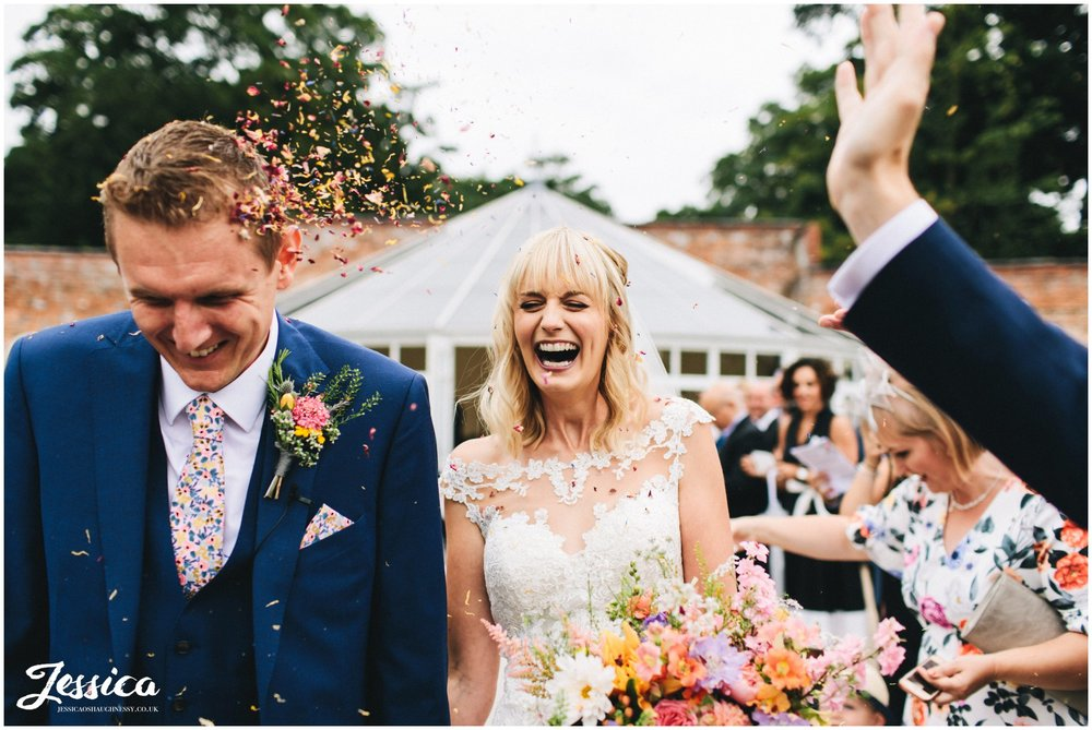 bride laughs as her guests throw confetti at her