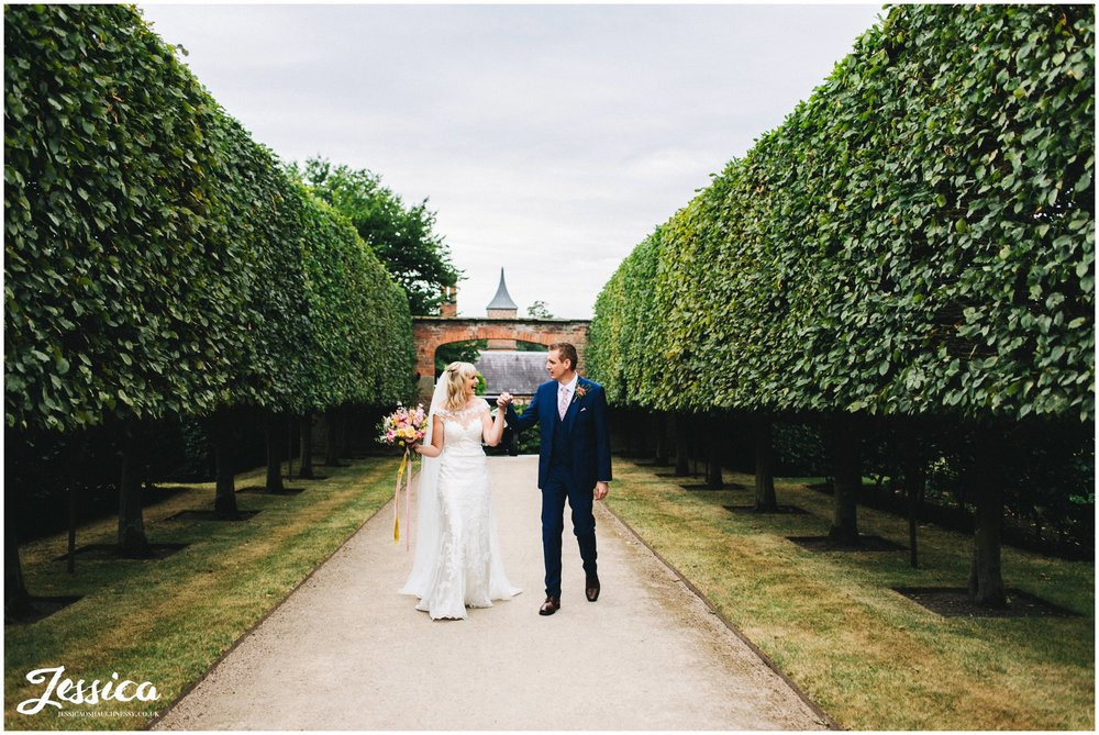 newlywed's walk through the tree lined path holding hands