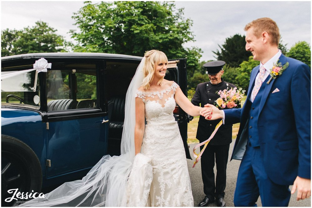 the groom helps his bride out of the wedding car