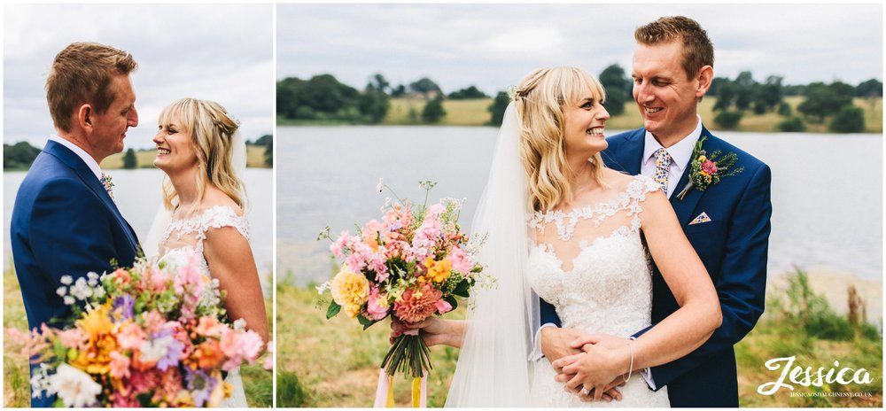 couple hug in front of the lake at combermere abbey after their wedding ceremony