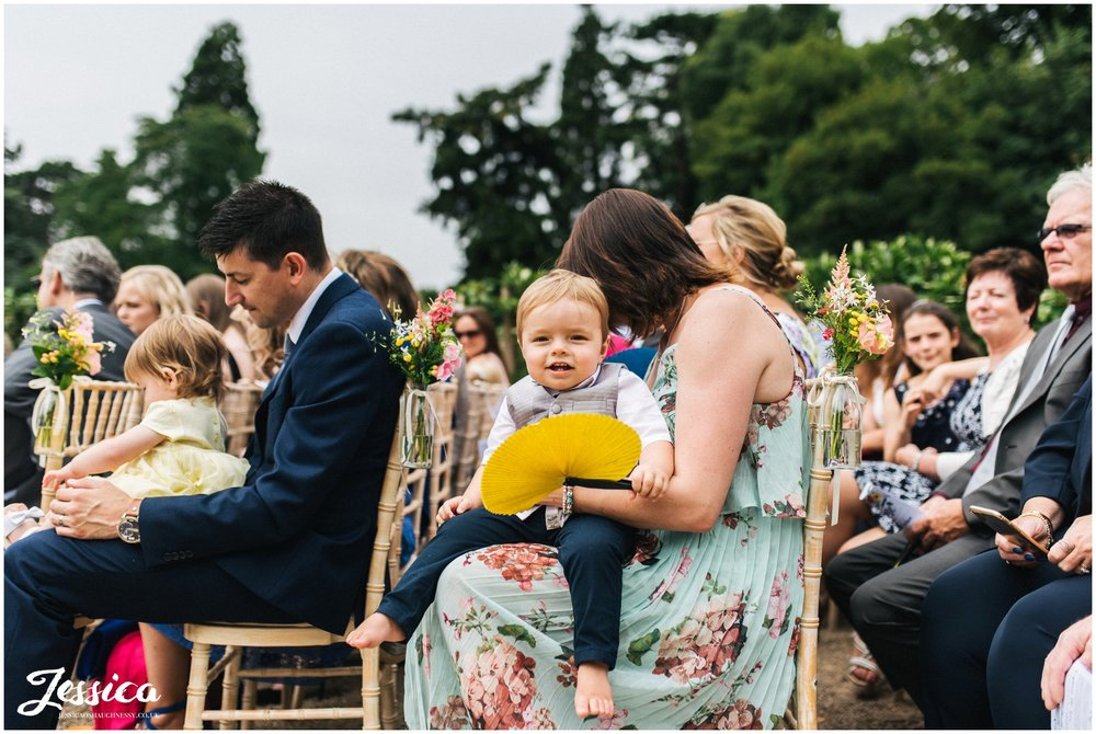 child sits on his mothers knee for the wedding service