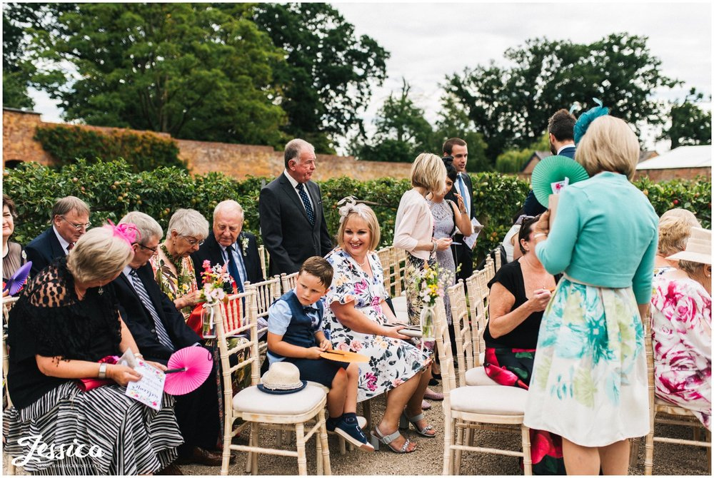 guests are seated at the ceremony at combermere abbey