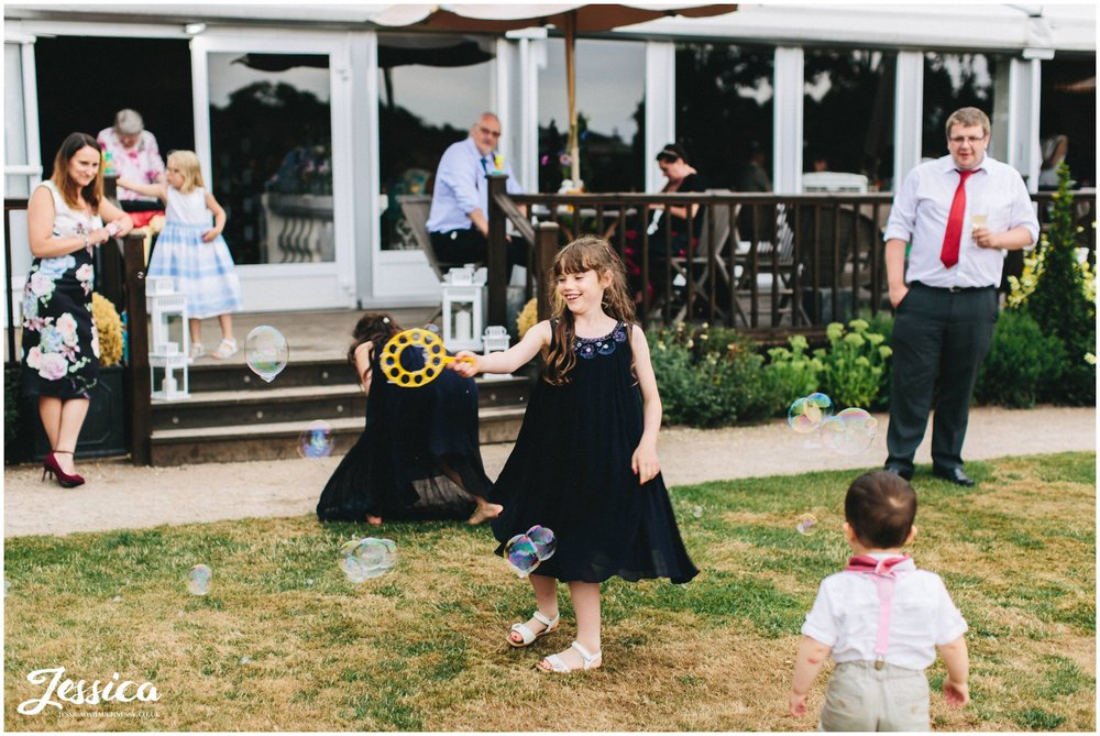 children play blowing bubbles at the cheshire wedding