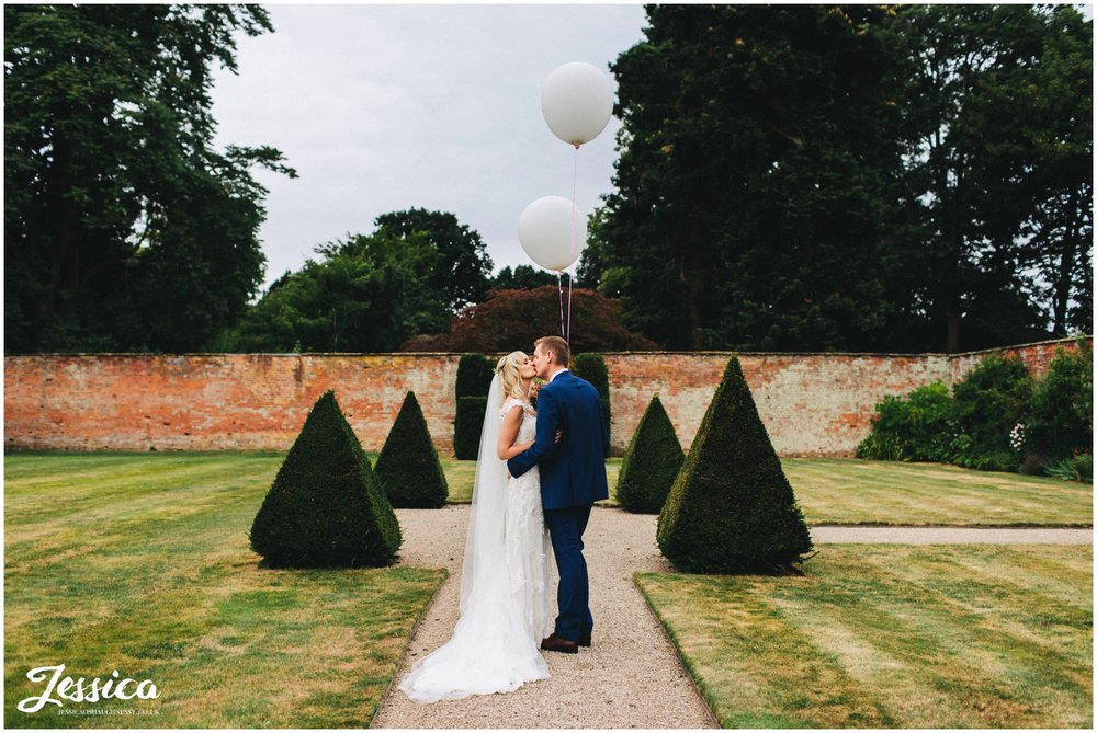 couple kiss in combermere abbey grounds holding balloons