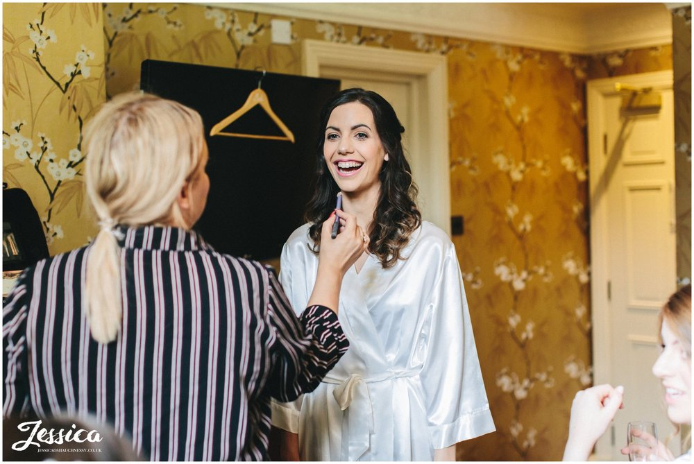 bride laughs as she gets her make up done