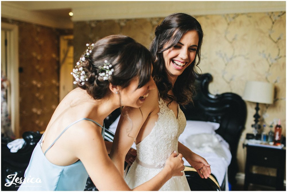 bride laughs with her sister as she gets into wedding dress