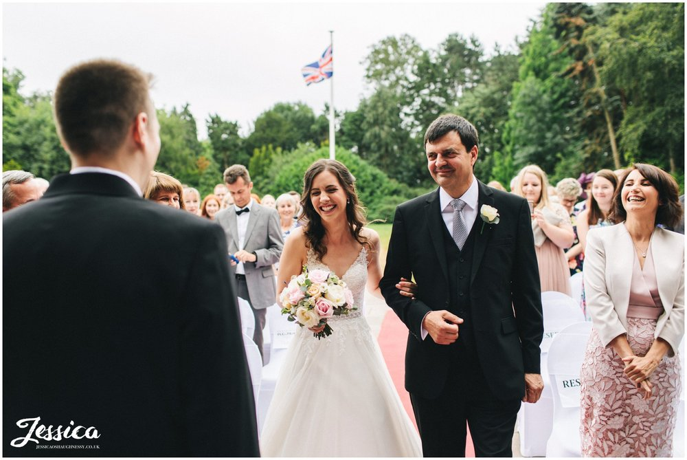 bride smiles as she see's her groom at inglewood manor in cheshire