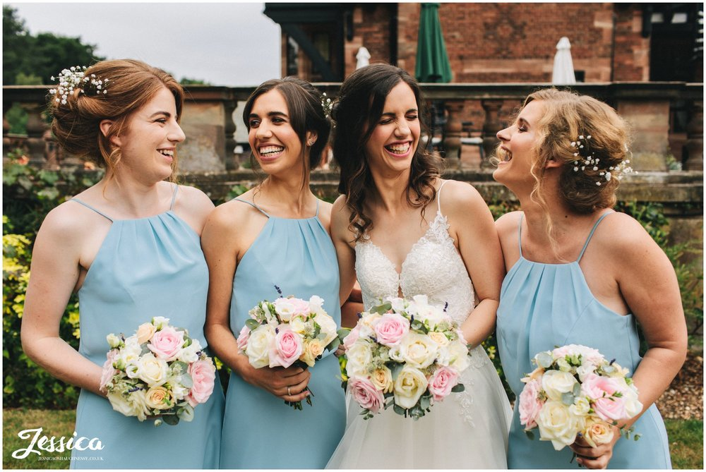 the bride laughs with her bridesmaids