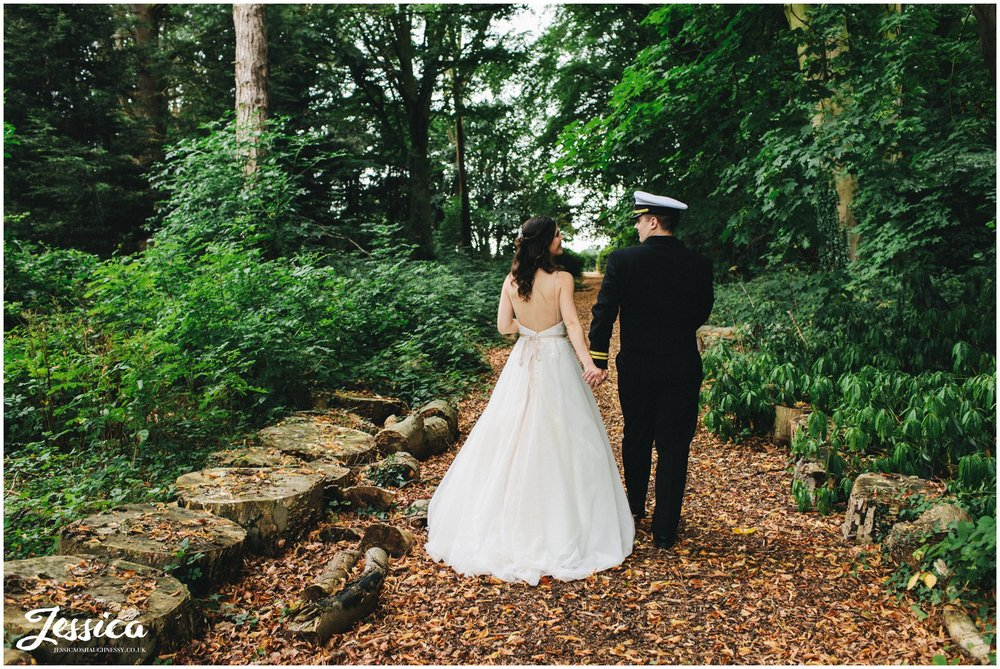 the new husband and wife hold hands walking through the forest
